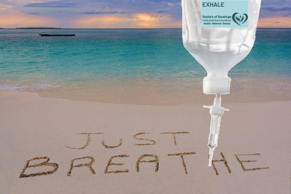 """Exhale - beach with """"Just Breathe"""" written in sand"""