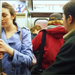 Woman holding bar in subway car looking nauseous