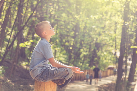 Boy sitting in sunlight with eyes closed