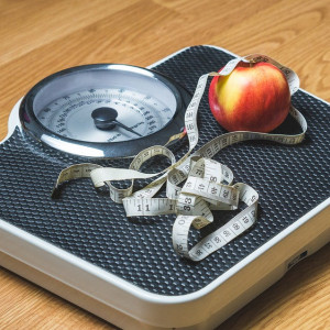 Weight loss - a scale with an apple and measuring tape on top